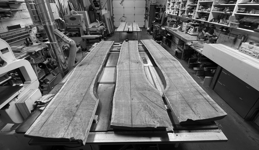 large lumber slabs layer out in fully equipped small space woodshop