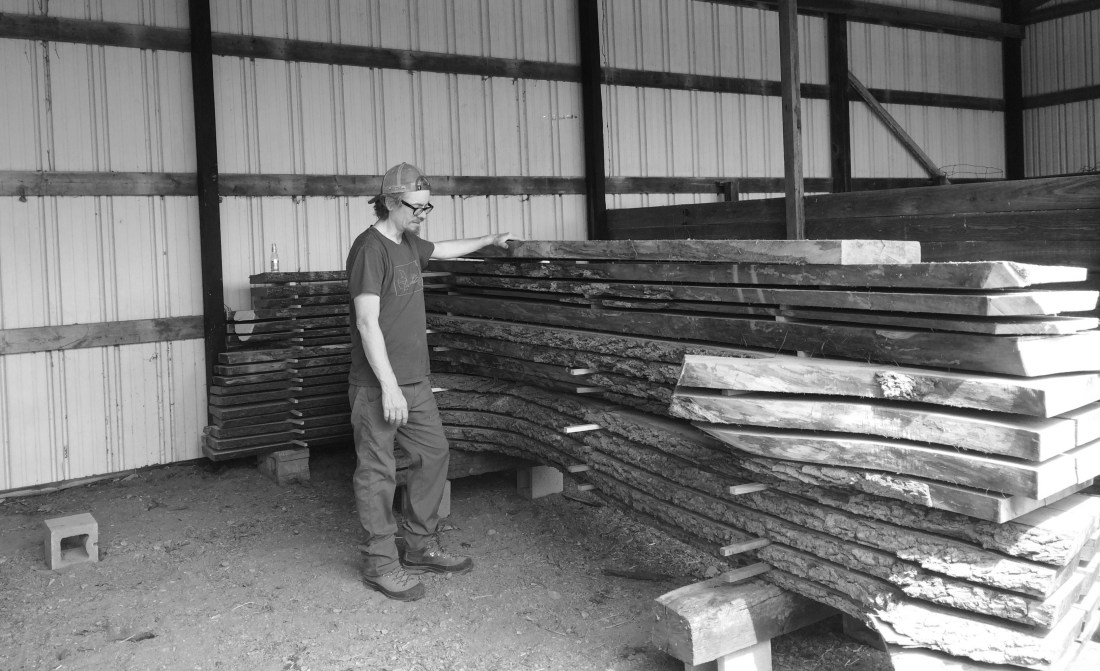 black and grey photo with man standing next to giant walnut lumber stack and white barn in background