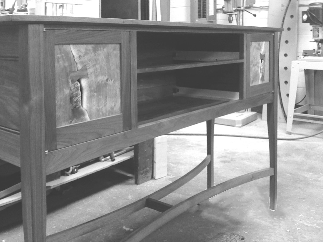 Black and grey mesquite and walnut side board construction with live edge door fronts and bow tie dutchman and woodshop in the background