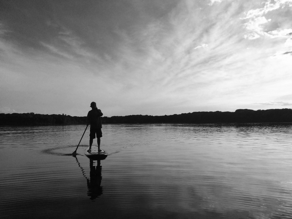 man on a handmade wooden stand up paddle board on a lake in black and grey photography