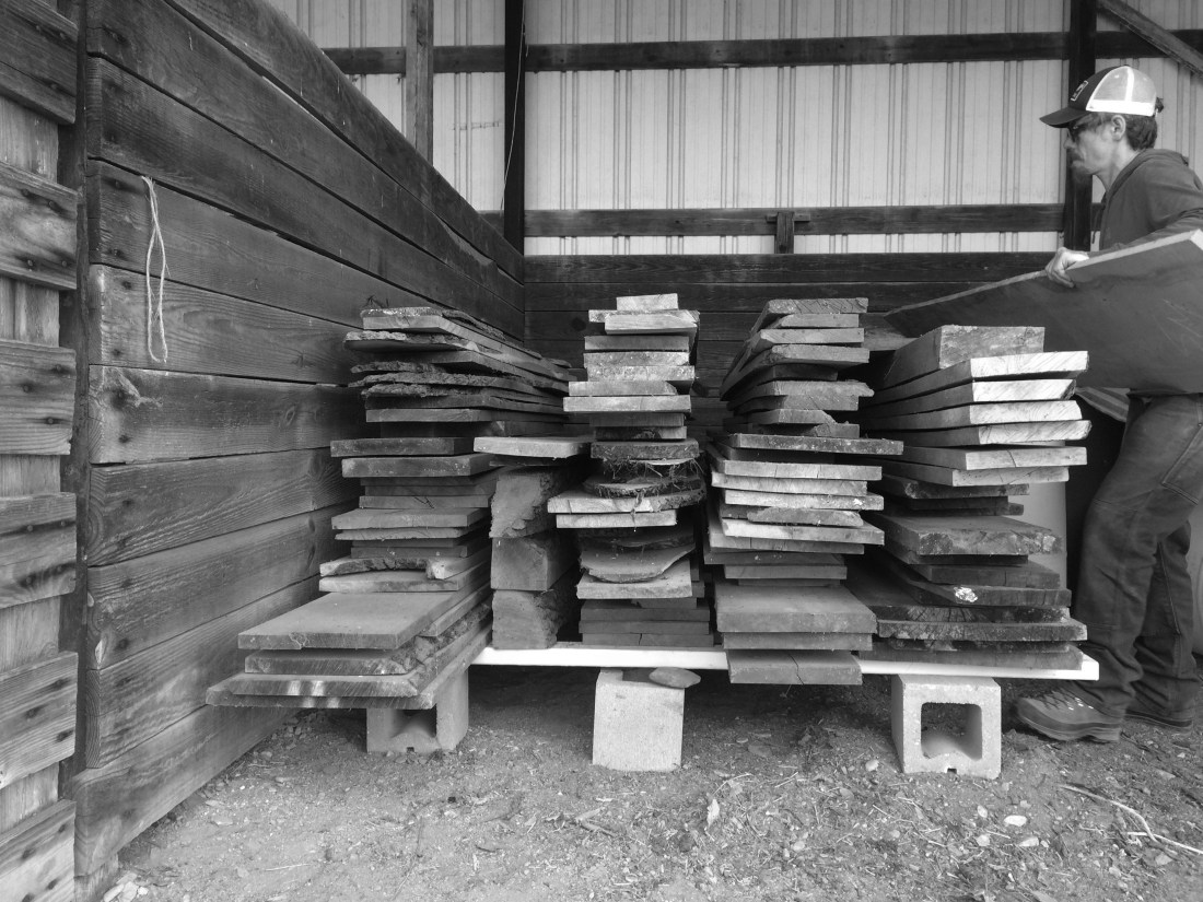 black and grey thin dimensioned lumber stack with man placing a large flat board on top with barn in the background