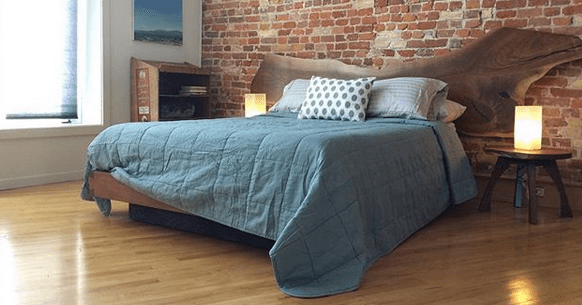 side view of walnut platform bed set and live edge headboard with turquoise comforter side table and lights