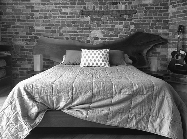 Live edge walnut headboard platform bed with two side tables and a brick wall in the background and hanging guitar