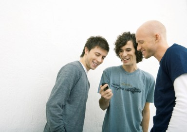 Young Man Showing Two Male Friends Cell Phone