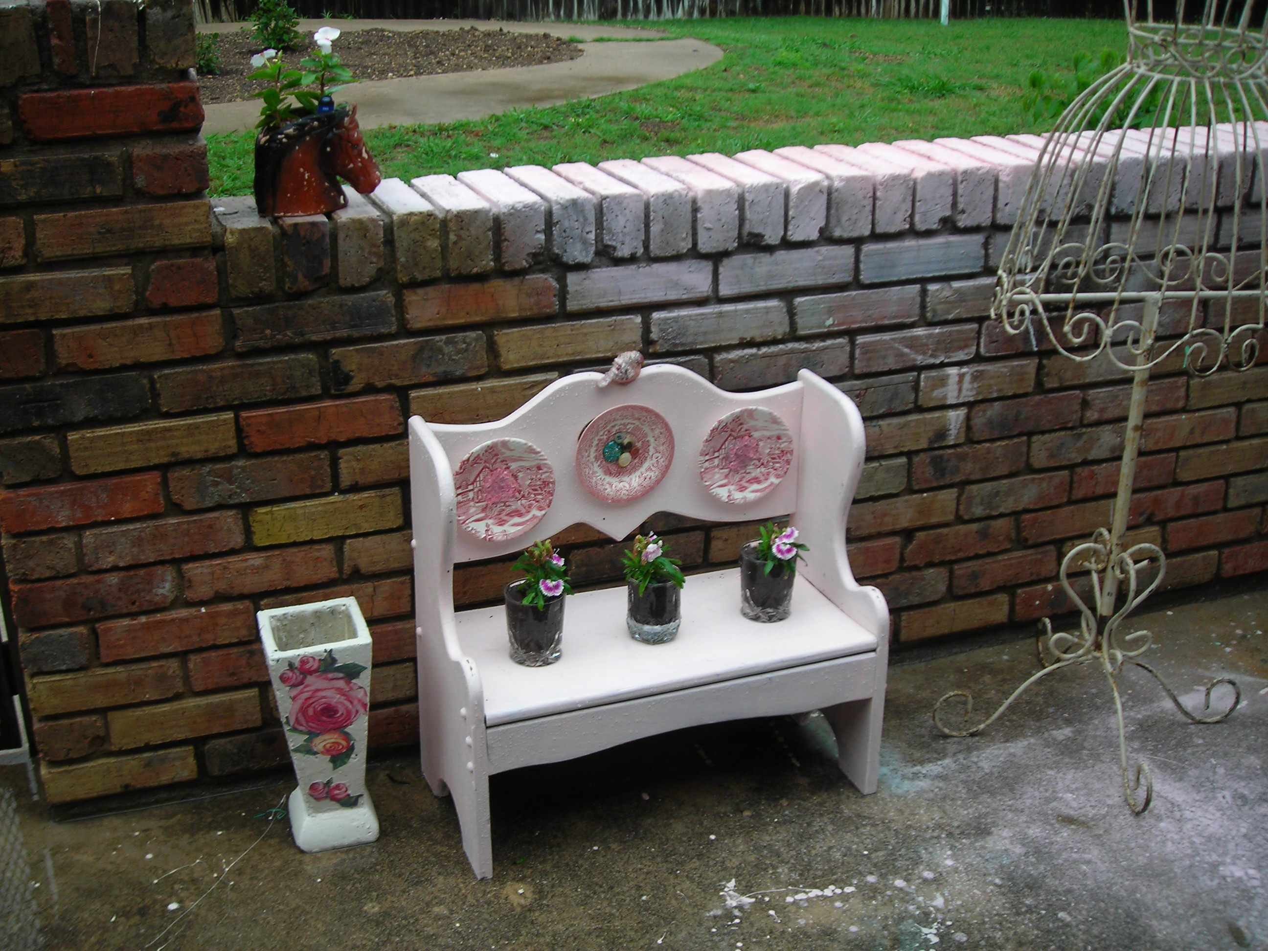 some pretties from my patio ... the little bench i found at the GW barn a few weeks ago. painted it out pink, attached some little plates and a birdie ... the little plants are from the lampasas sale, the rose vase is from the hh sale