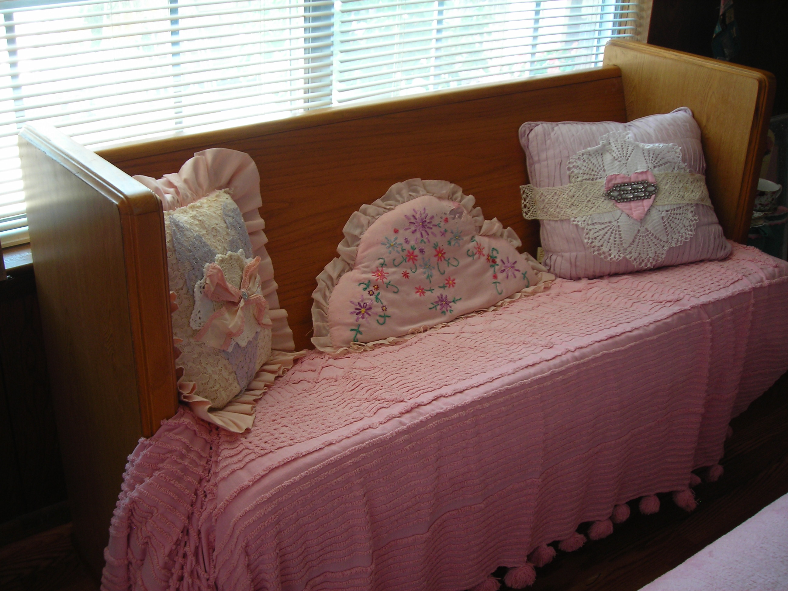 here's the church bench i mentioned in an earlier blog. found a great place for it too. in my b'fast nook! covered the cushion with an old pink chenille spread, added some sweet pillows. makes a wonderful sitting or reading area (or you may pray if you wish)