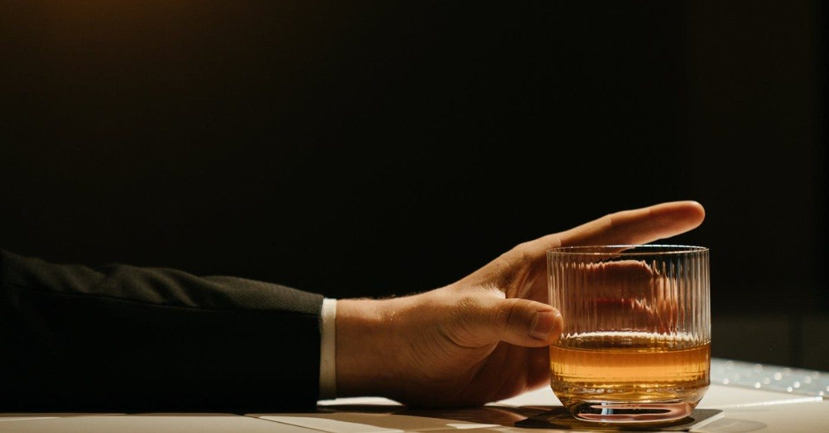 A man's arm holding a glass of whiskey