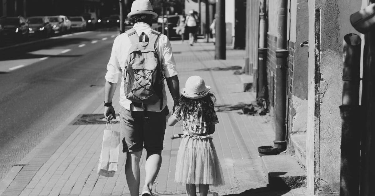 black and white back shot of father and daughter holding hands and walking