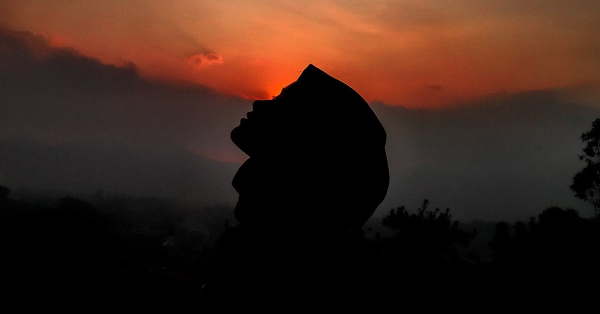 Face silhouette of a woman against the setting sun in the background