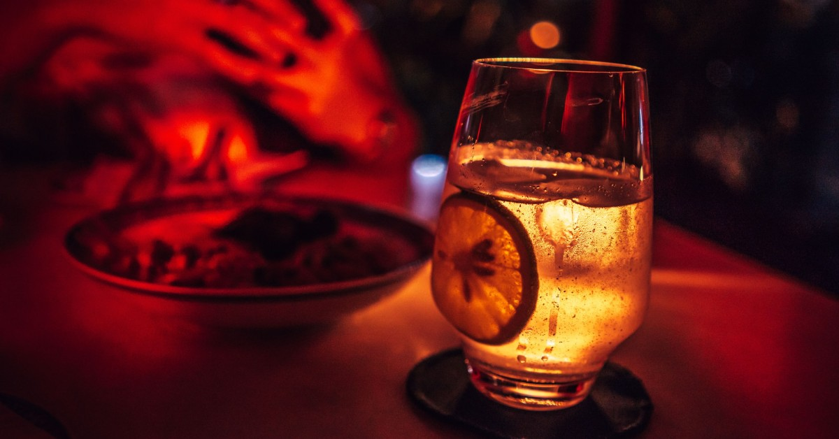 A glass of vodka with a lemon in it and red lighting