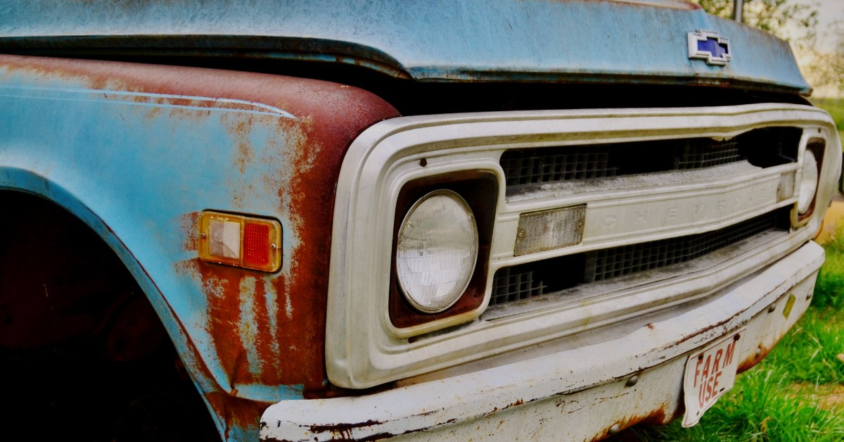 The front bumper of an old and rusted Chevy