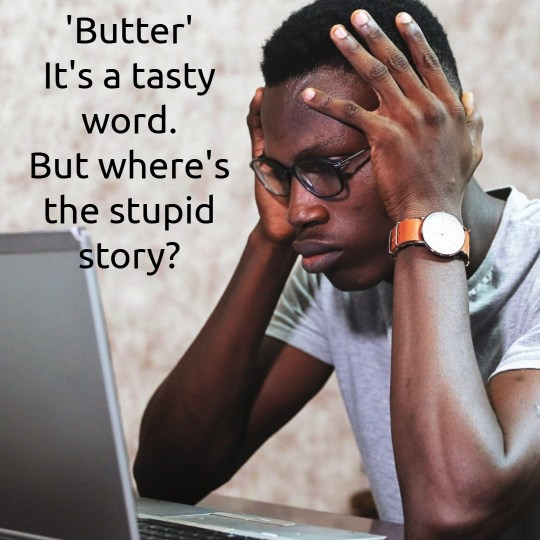A black man with glasses, gripping his head with his hands, staring at a laptop screen