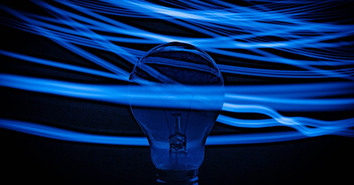 A light bulb with rays of blue light crisscrossing around it