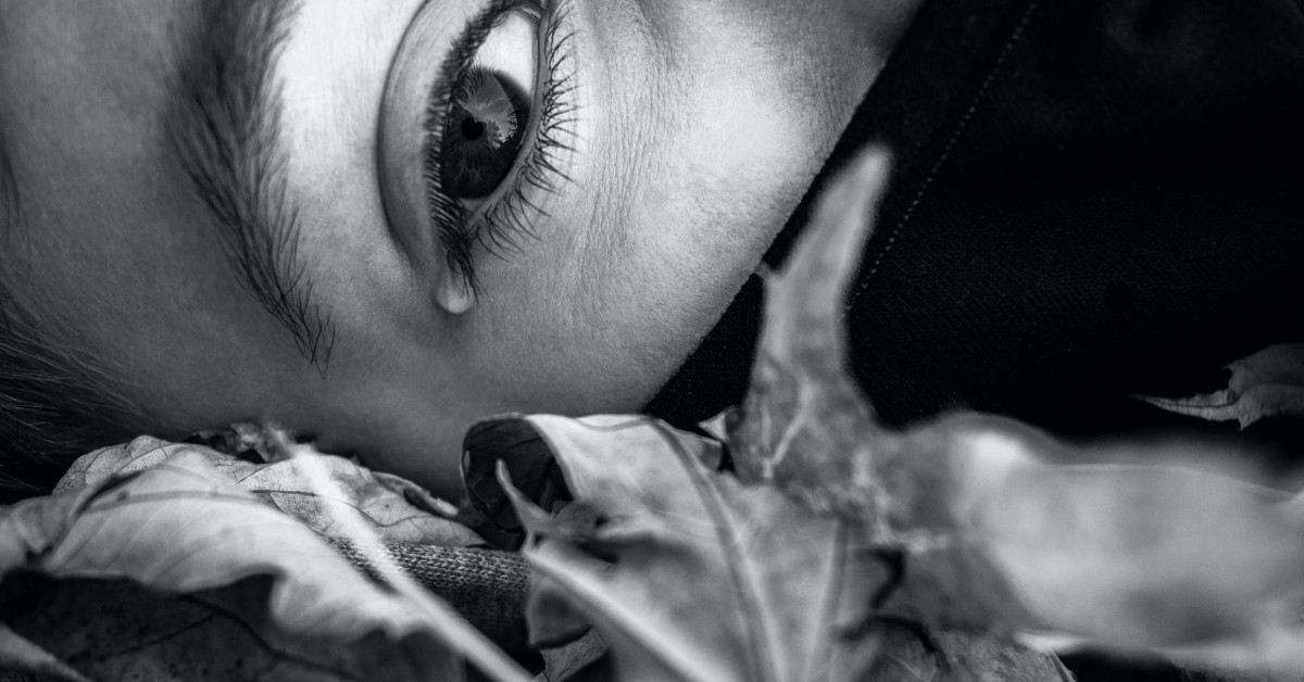 A black and white close up of a woman's eye with a tear rolling out