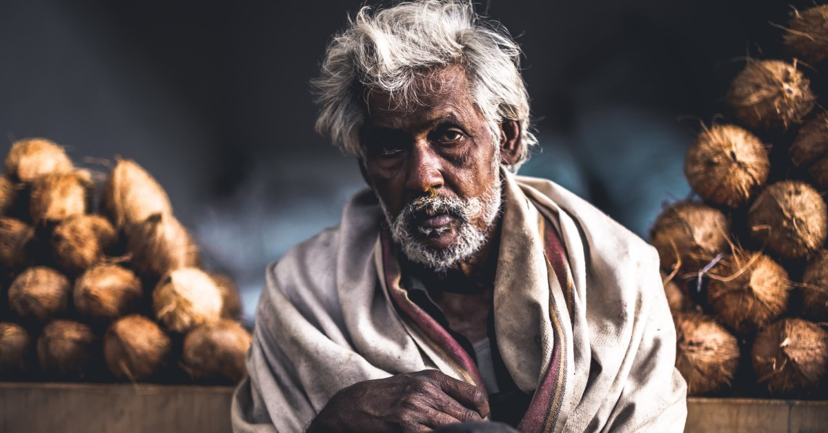 An old Indian man with whit hair sitting and looking tired
