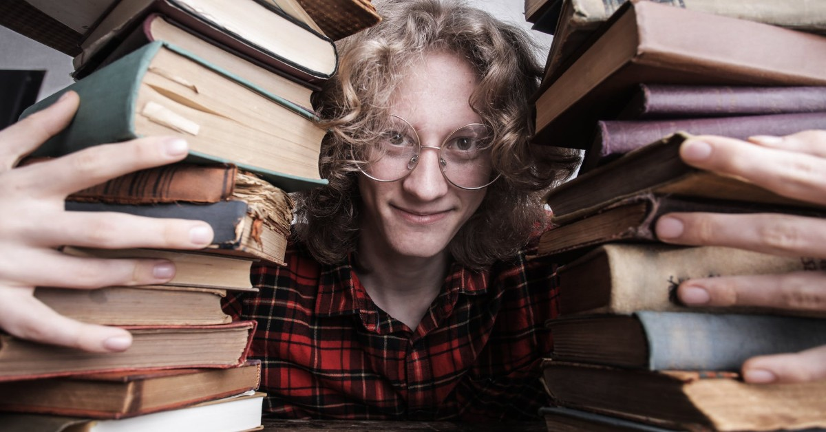 A young man wearing glasses and peeking out from between two tall piles of books