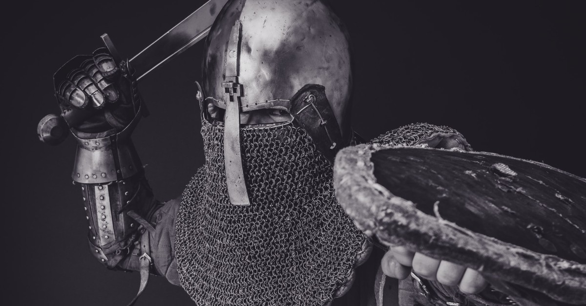 A white man dressed in knight's armor holding a shield and swinging his sword