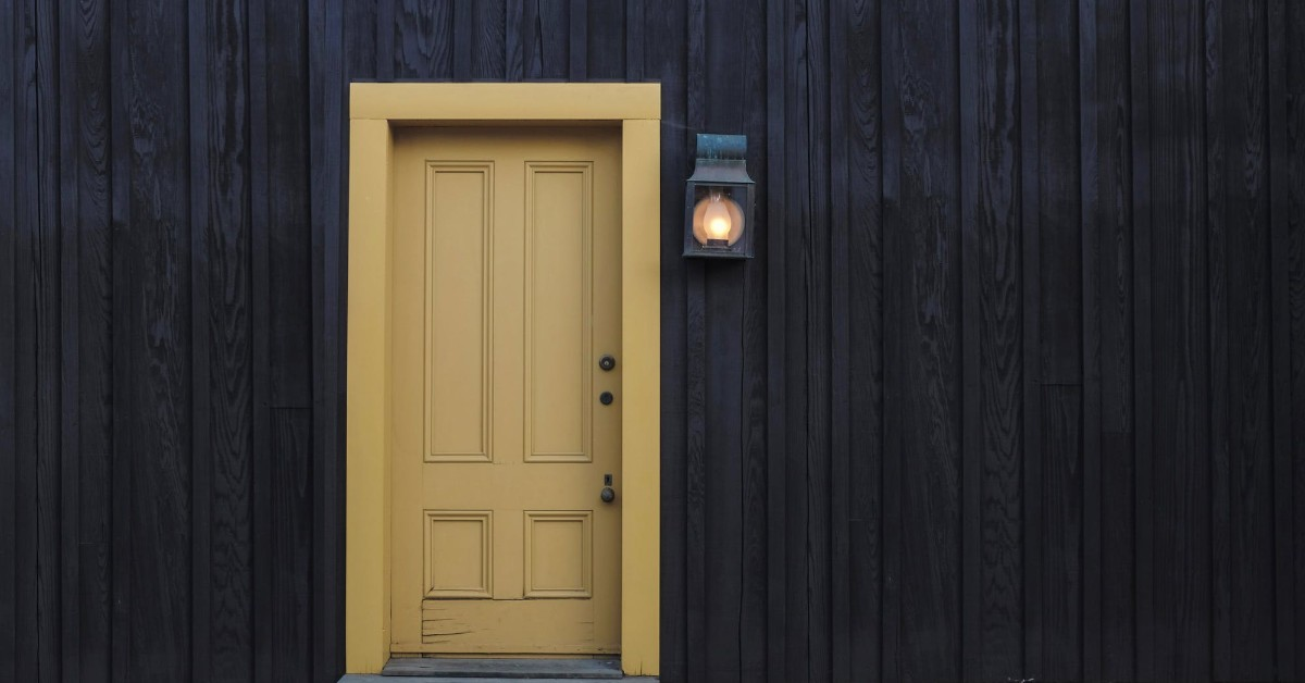 A cream-yellow door in a grey slated exterior wall with a porch light next to it