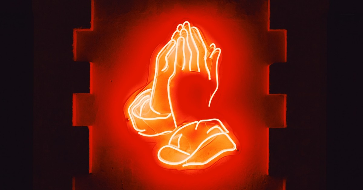 A bright orange neon sign of folded hands in prayer