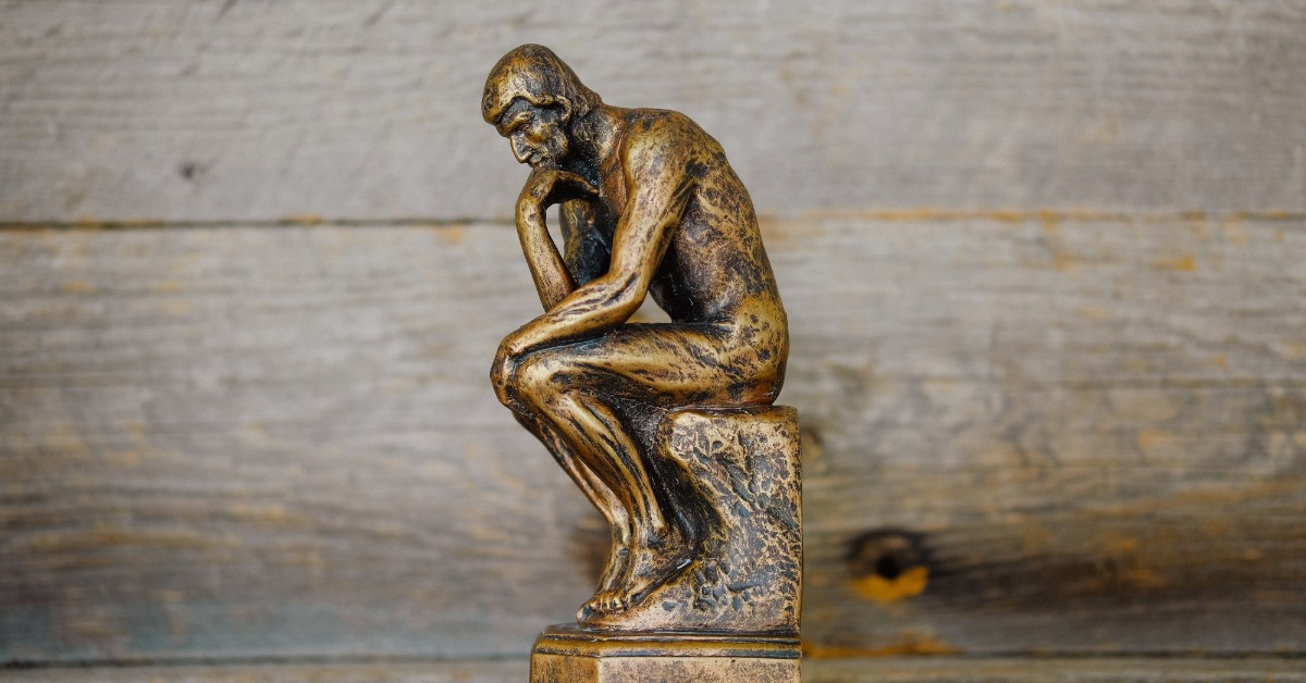 The bronze sculpture of The Thinker against a wooden backdrop
