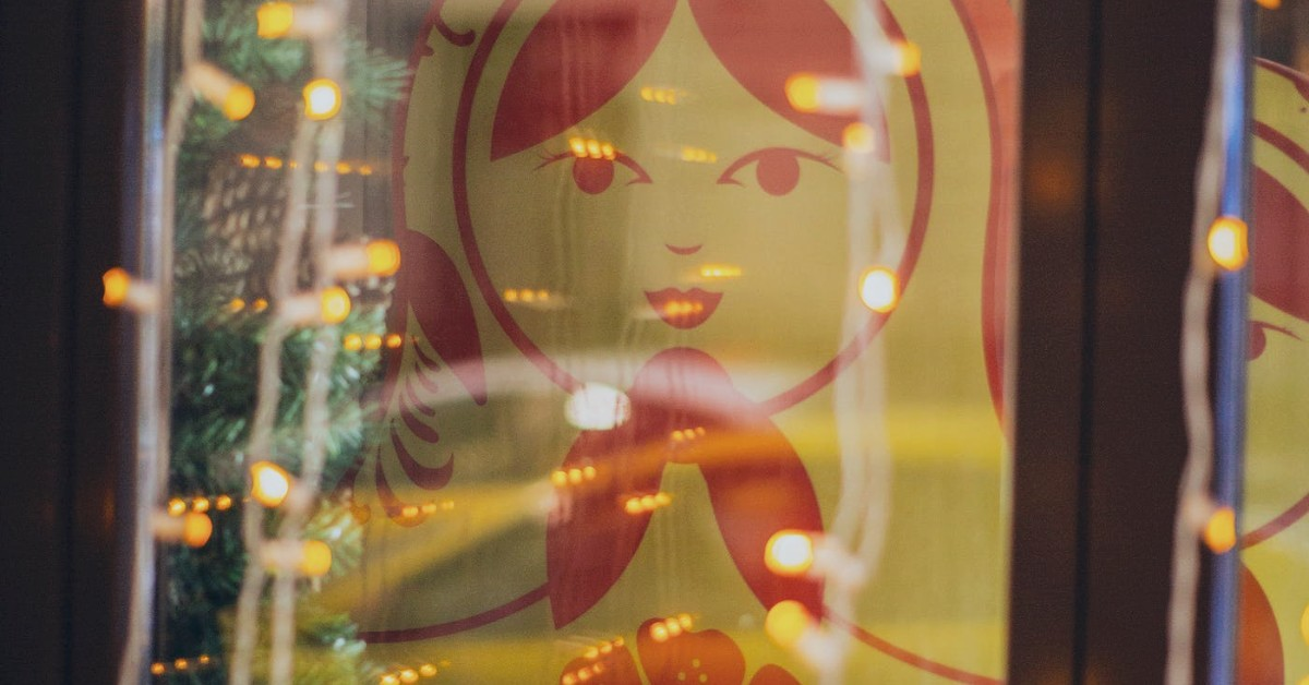 The cartoon of a girl face and scarf around her neck with strands of lights in the foreground