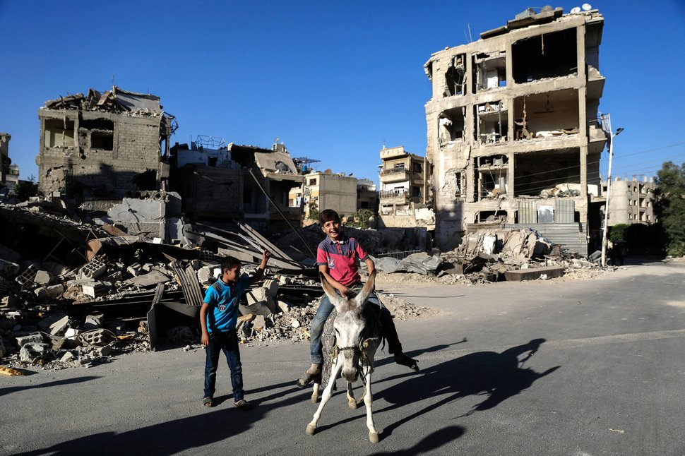 TOPSHOT - Syrian boy rides a donkey as they play in the rebel-held town of Douma, on the eastern edges of the capital Damascus, on the second day of Eid al-Adha Muslim holiday on September 13, 2016. / AFP / Sameer Al-Doumy        (Photo credit should read SAMEER AL-DOUMY/AFP/Getty Images)