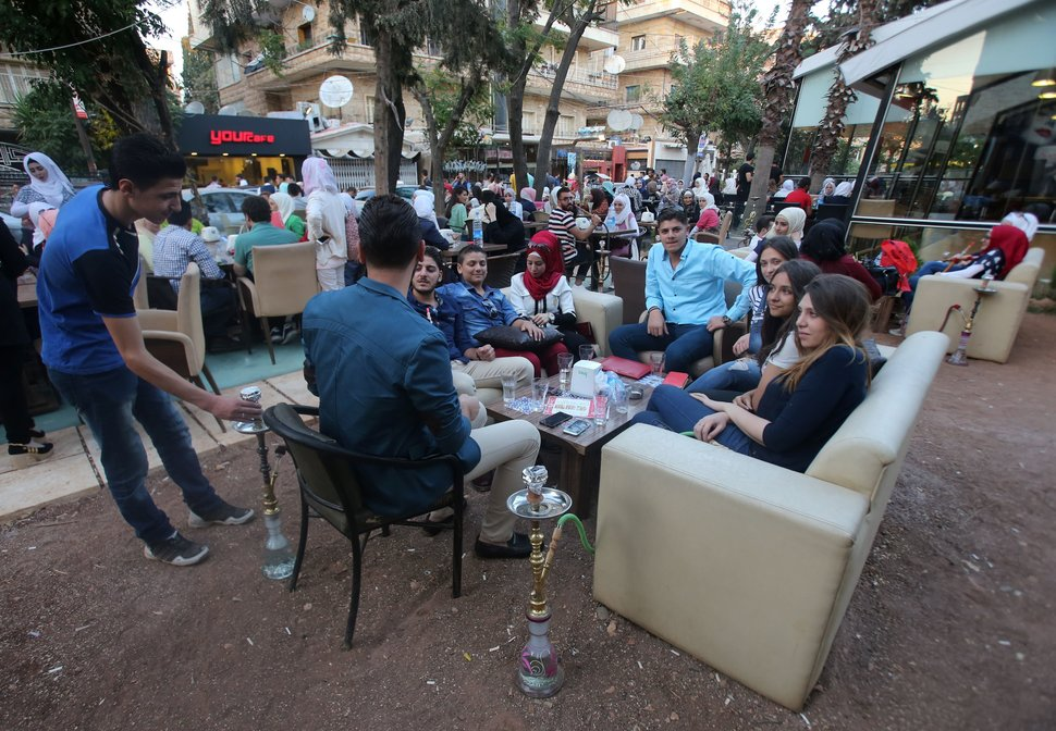 Syrian youths sit at a cafe in the government-held Mogambo neighbourhood of the northern Syrian city of Aleppo as they celebrate the Eid al-Adha Muslim holiday on September 13, 2016, a day after a fragile ceasefire was brokered. In the government-held western Aleppo, which is regularly targeted by rebel rocket fire, residents enjoyed the quiet of the morning and expressed hope that the truce would last.  / AFP / Youssef KARWASHAN        (Photo credit should read YOUSSEF KARWASHAN/AFP/Getty Images)
