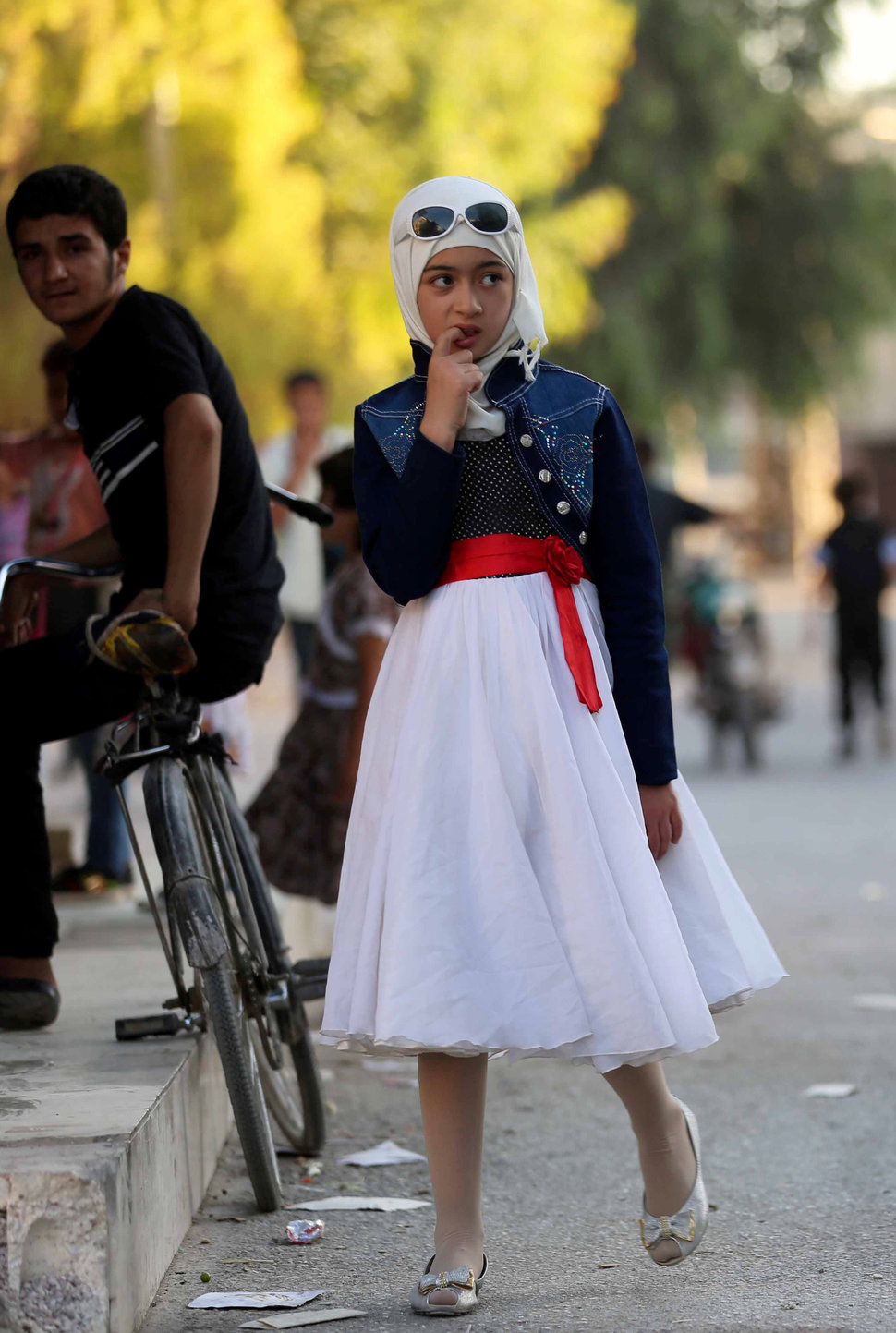 A Syrian girl walks in the street in the Syrian rebel-held town of Arbin, in the eastern Ghouta region on the outskirts of the capital Damascus, as they celebrate the Muslim Eid al-Adha holiday on September 13, 2016, the day after an internally backed ceasefire for Syria came into effect as part of a hard-fought deal to bring an end to the war between rebels and regime fighters.  / AFP / AMER ALMOHIBANY        (Photo credit should read AMER ALMOHIBANY/AFP/Getty Images)