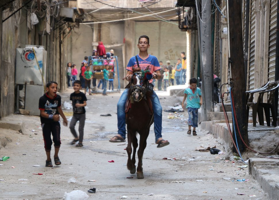 TOPSHOT - A Syrian boy rides a horse as Syrian children play in the street in a rebel-held area  of the northern Syrian city of Aleppo as they celebrate the Eid al-Adha (Feast of the Sacrifice) holiday on the first day of a fragile ceasefire which aims to bring an end to fighting between loyalists to the Syrian president and a wide range of rebels but excludes jihadist forces like the Islamic State group. AFP correspondents in both the rebel-held east and the government-held west reported nearly 24 hours had passed without air strikes or rocket fire.  / AFP / THAER MOHAMMED        (Photo credit should read THAER MOHAMMED/AFP/Getty Images)