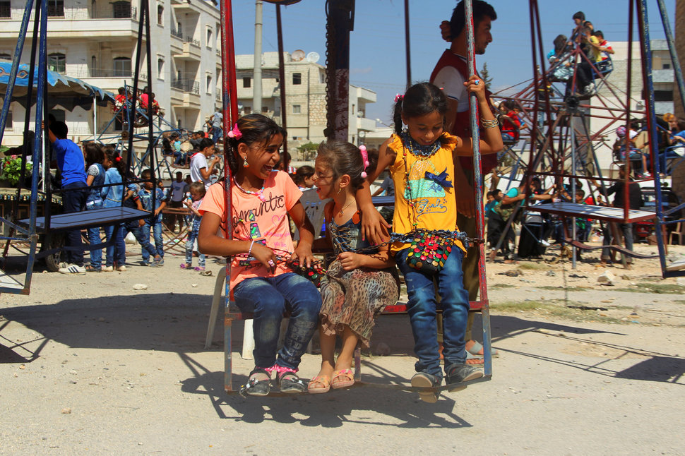 Children play on swings on the third day of Eid al-Adha in the rebel controlled city of Idlib, Syria September 14, 2016. REUTERS/Ammar Abdullah
