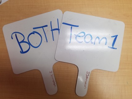 """Two whiteboard paddles with """"team 1"""" and """"Both"""" written on them."""