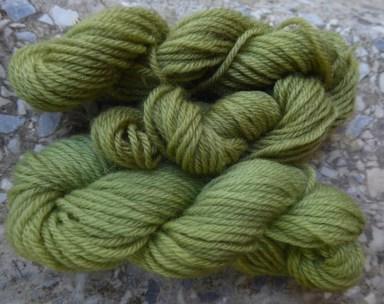2 green miniskeins of wool, the top one is slightly darker than the bottom one.