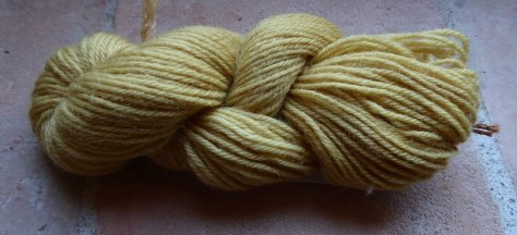 A picture of a pale yellow/beige skin of yarn photographed on a terracotta tile windowsill