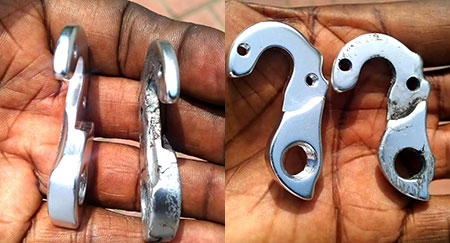 The side-by-side comparison of the new derailleur hanger on the left and old one on the right shows the cracks in the old derailleur.