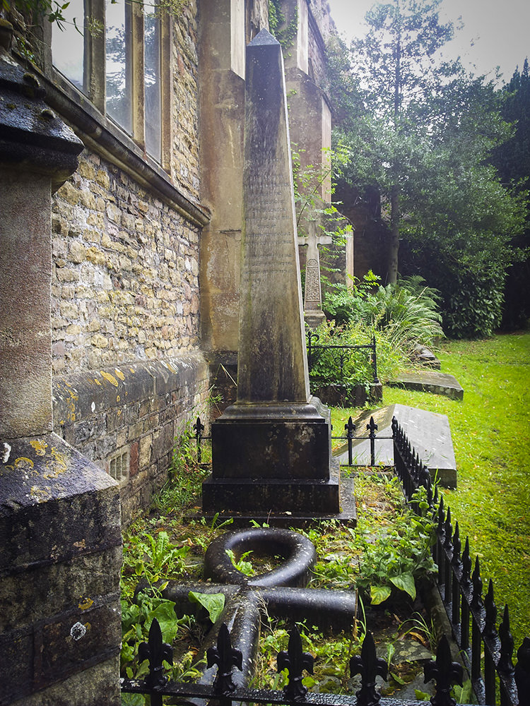 A grave with an obelisk-shaped stone and an Egyptian ankh lying flat in front of it. The grave is flush up against the side of the church