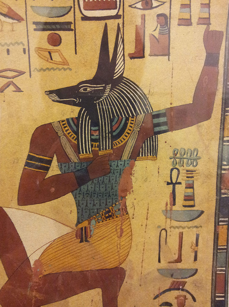 A jackal-headed human soul, kneeling, with his right hand to his chest and left hand up in the air behind his head.