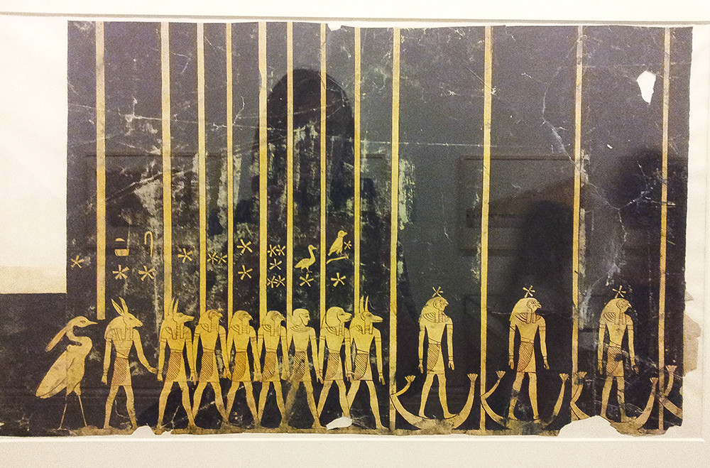 Rows of yellow-coloured gods standing in a row on a dark background. Above some of the figures are stars