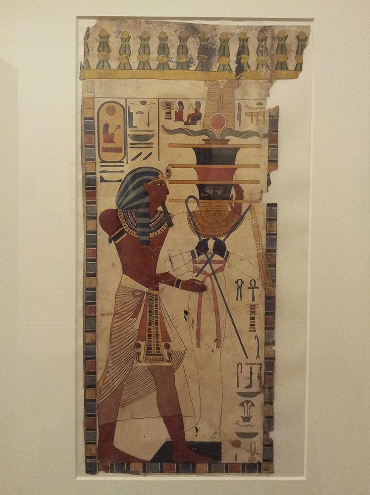 Seti wearing a white kilt and Nemes-headdress standing before Osiris as a mummy with a djed-shaped head