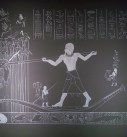A closeup of the wall mural - a dark grey background with the scene painted in white. The scene shows a man hunting fish in marshes with a double-pronged spear, with birds flying above him