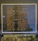 A badly damaged papyrus with text written in black ink. The papyrus is held within glass panels with a wooden frame