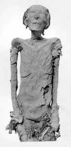 A mummy of an Egyptian woman. She's mostly unwrapped with the remains of linen wrappings around her arms and lower body.