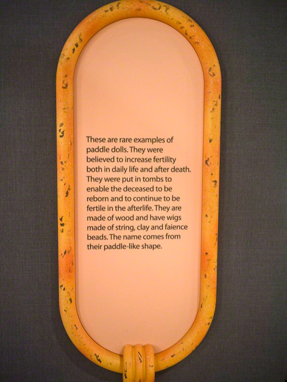 A cartouche-shaped information panel talking about paddle dolls