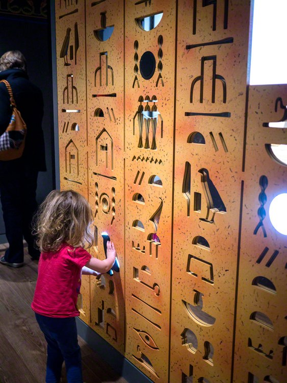 The young girl playing with the hieroglyph shapes on a wall