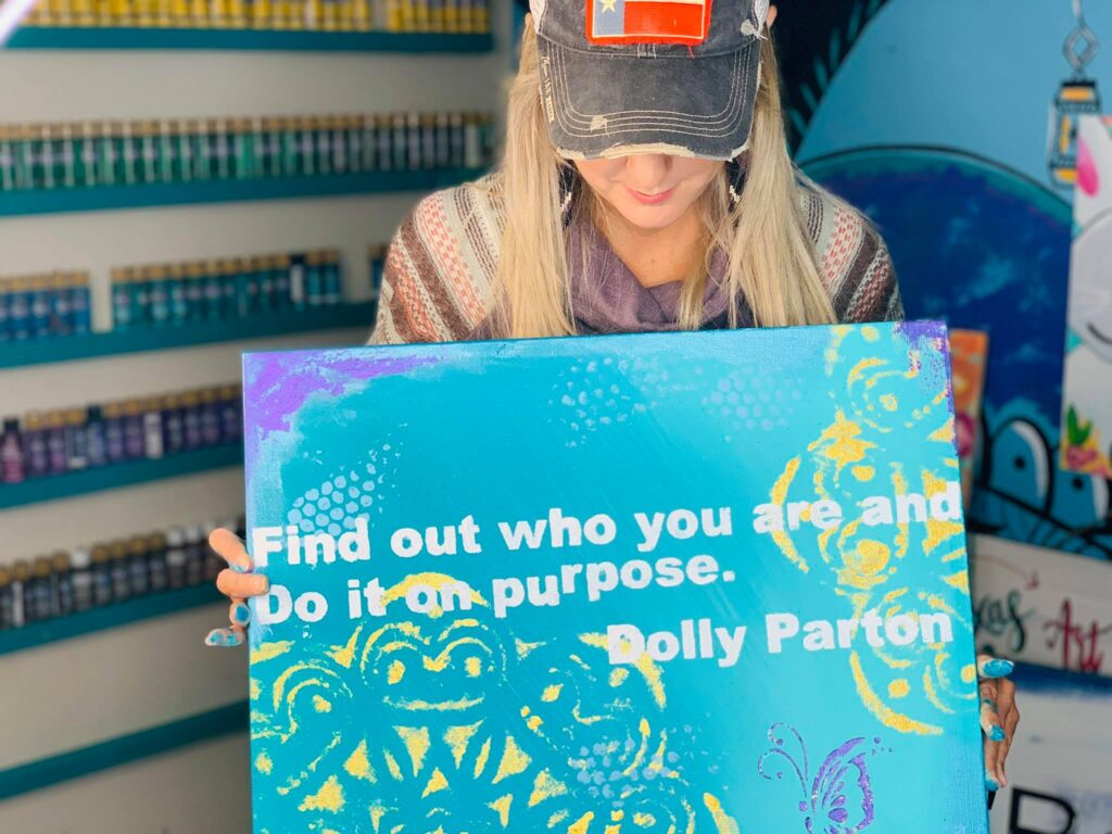 "Woman holding hand painted Dolly Parton quote ""find out who you are and do it on purpose""."