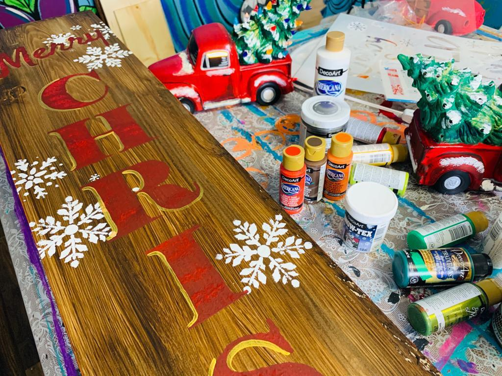 Merry christmas porch sign next to acrylic paints