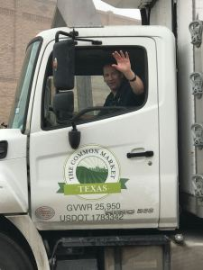 Jon, the delightful driver of the Common Market delivery truck waving from his truck cab.
