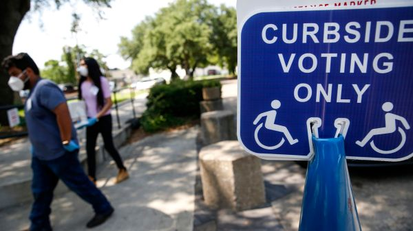 High school poll workers Sebastian Roman (left), 18, and Diana Paulin, 18, work a curbside voting lane during early voting at Beckley Courthouse on Thursday, July 9, 2020 in Dallas.(Ryan Michalesko / Staff Photographer)