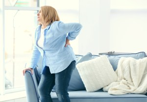 woman suffering from backache at home