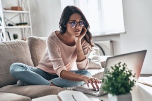 woman in eyewear using computer while sitting on the sofa at home