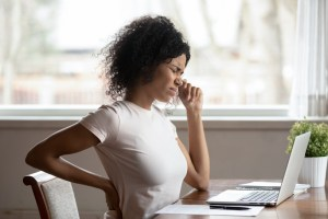 woman sitting at desk experiencing back pain